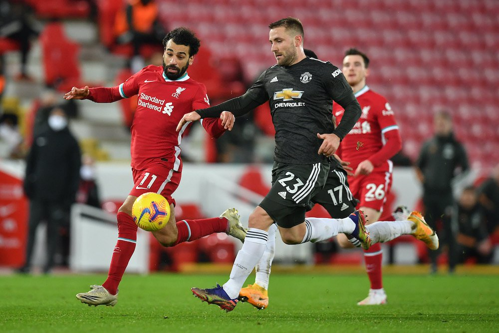 LIVERPOOL, ENGLAND – JANUARY 17: Luke Shaw of Manchester United  is put under pressure by Mohamed Salah of Liverpool during the Premier League match between Liverpool and Manchester United at Anfield on January 17, 2021 in Liverpool, England. Sporting stadiums around England remain under strict restrictions due to the Coronavirus Pandemic as Government social distancing laws prohibit fans inside venues resulting in games being played behind closed doors. (Photo by Paul Ellis – Pool/Getty Images)