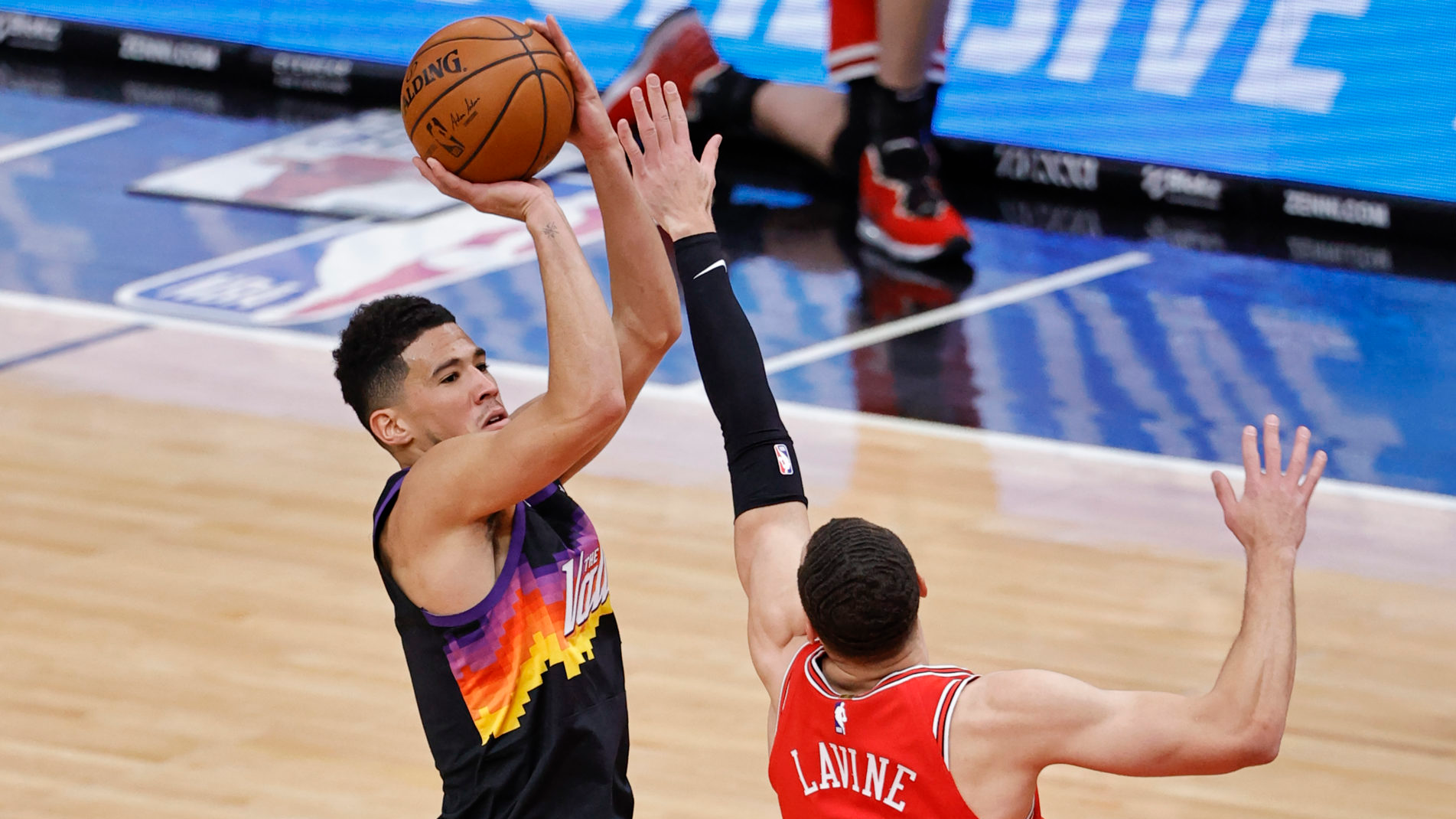 Feb 26, 2021; Chicago, Illinois, USA; Phoenix Suns guard Devin Booker (1) shoots against Chicago Bulls guard Zach LaVine (8) during the first half of an NBA game at United Center. Mandatory Credit: Kamil Krzaczynski-USA TODAY Sports