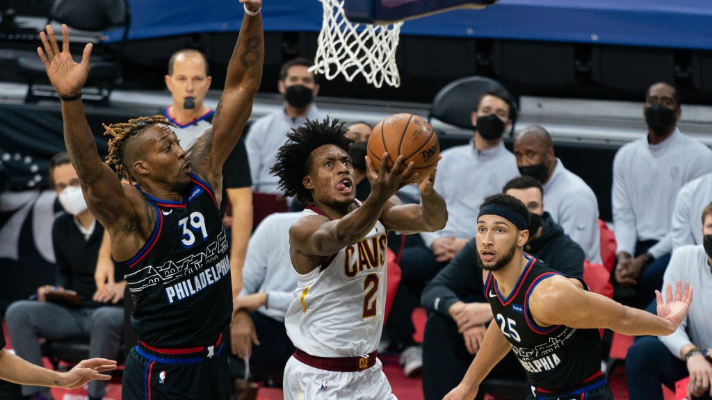 Feb 27, 2021; Philadelphia, Pennsylvania, USA; Cleveland Cavaliers guard Collin Sexton (2) drives for a score past Philadelphia 76ers center Dwight Howard (39) and guard Ben Simmons (25) during the second quarter at Wells Fargo Center. Mandatory Credit: Bill Streicher-USA TODAY Sports