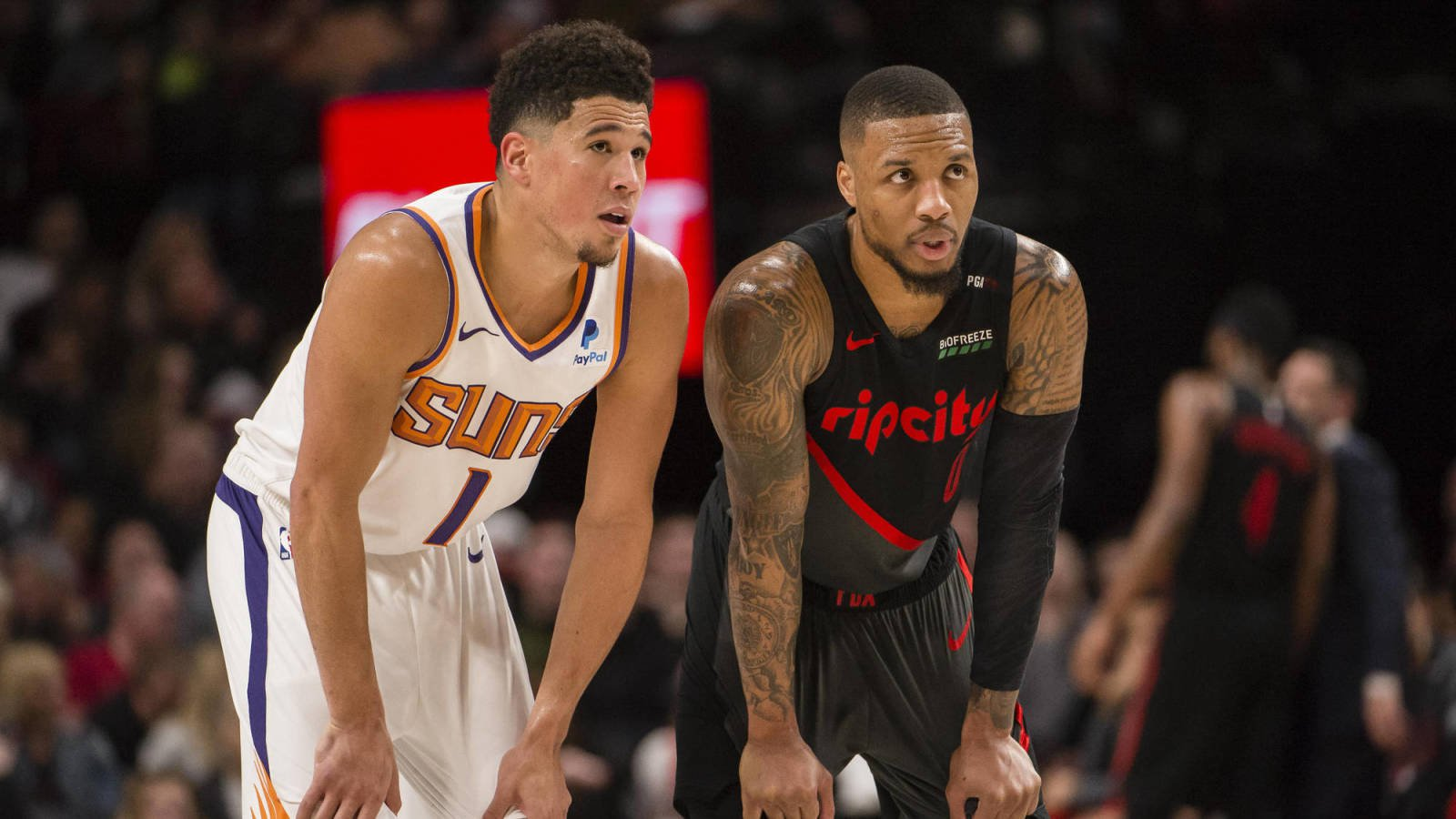 Mar 9, 2019; Portland, OR, USA; Phoenix Suns guard Devin Booker (1) and Portland Trail Blazers guard Damian Lillard (0) talk during a break in action during the second half at Moda Center. The Trail Blazers beat the Suns 127-120. Mandatory Credit: Troy Wayrynen-USA TODAY Sports