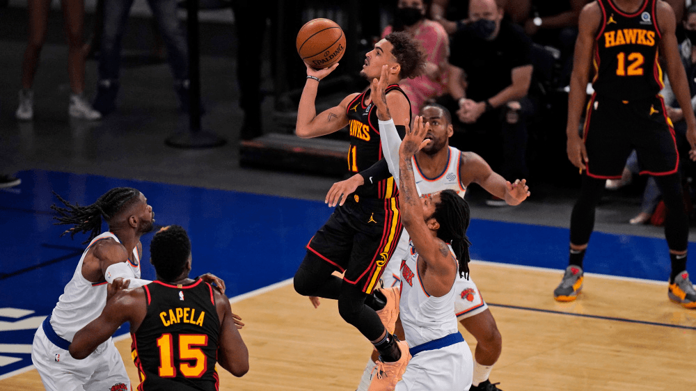 Atlanta Hawks' Trae Young, center, drives to the basket during the first half of Game 1 of an NBA basketball first-round playoff series against the New York Knicks, Sunday, May 23, 2021, in New York. (AP Photo/Seth Wenig, Pool) ORG XMIT: NYSW736