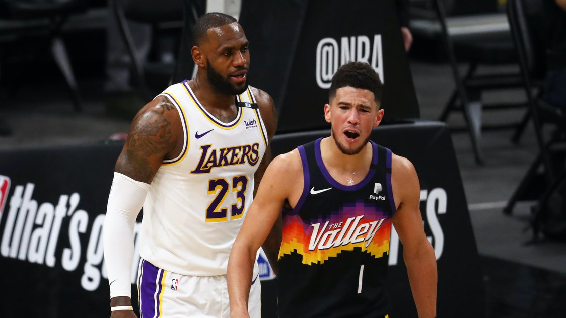 May 23, 2021; Phoenix, Arizona, USA; Phoenix Suns guard Devin Booker (1) reacts alongside Los Angeles Lakers forward LeBron James (23) in the first half during game one in the first round of the 2021 NBA Playoffs. at Phoenix Suns Arena. Mandatory Credit: Mark J. Rebilas-USA TODAY Sports